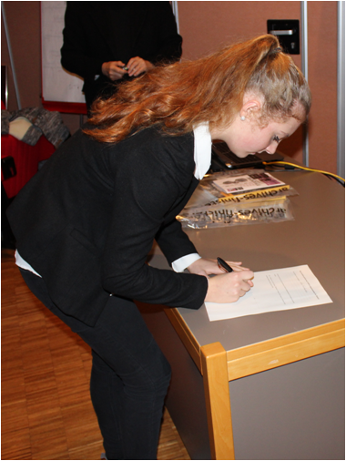 Ninon appose sa signature sur le document officiel du don